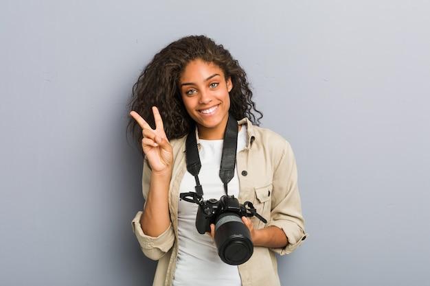 Mulher jovem fotógrafo americano africano com câmera mostrando sinal de vitória e sorrindo amplamente.