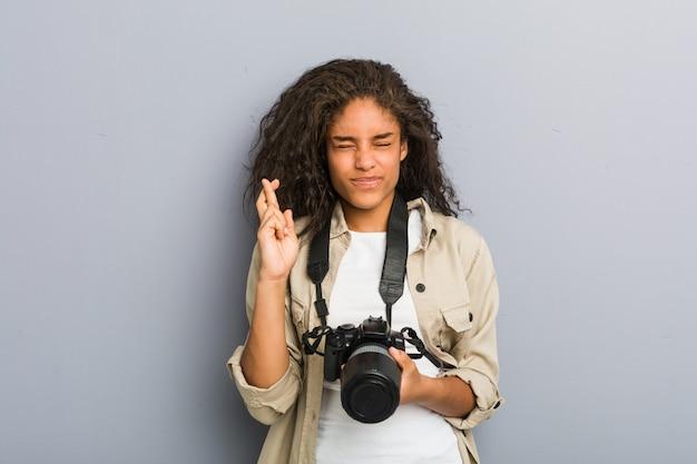 Mulher jovem fotógrafo americano africano segurando uma câmera cruzando os dedos por ter sorte