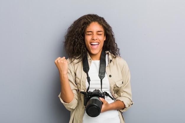 Mulher jovem fotógrafo americano africano, segurando uma câmera torcendo despreocupado e animado. conceito de vitória
