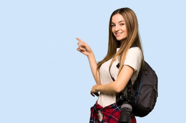 Mulher jovem fotógrafo apontando o dedo para o lado em posição lateral na parede azul isolada