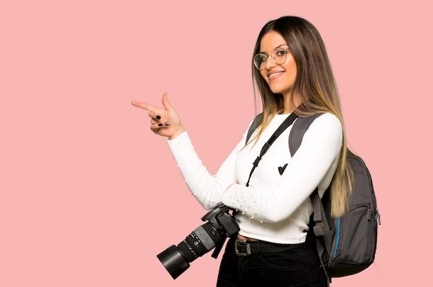 Mulher jovem fotógrafo apontando o dedo para o lado em posição lateral na parede rosa isolada