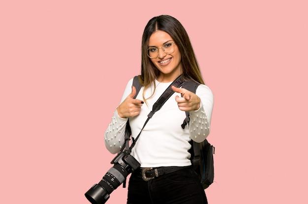 Mulher jovem fotógrafo apontando para a frente e sorrindo na parede rosa isolada