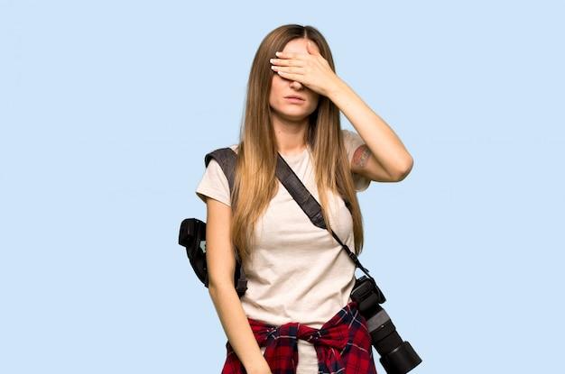 Mulher jovem fotógrafo cobrindo os olhos pelas mãos. não quero ver algo na parede azul