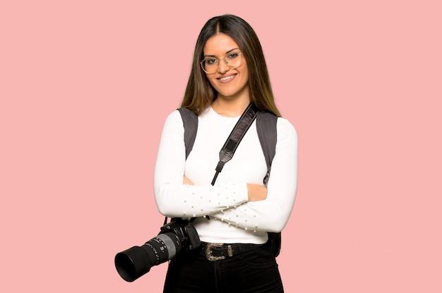 Mulher jovem fotógrafo com óculos e feliz na parede rosa isolada