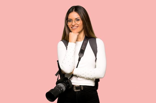 Mulher jovem fotógrafo com óculos e sorrindo na parede rosa isolada
