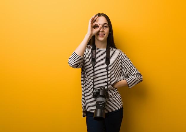 Mulher jovem fotógrafo confiante fazendo okey gesto no olho