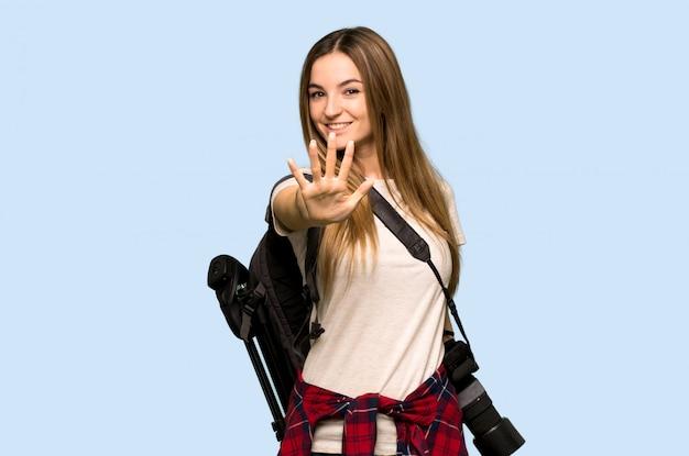 Mulher jovem fotógrafo contando cinco com os dedos na parede azul isolada