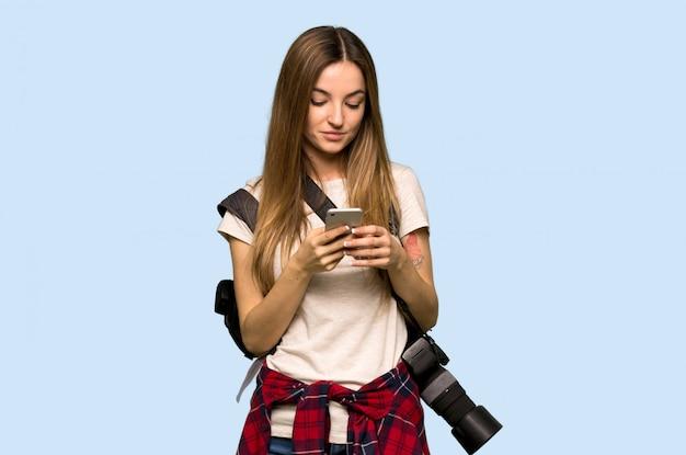 Mulher jovem fotógrafo enviando uma mensagem com o celular na parede azul isolada