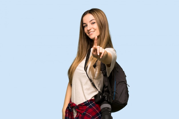 Mulher jovem fotógrafo mostrando e levantando um dedo na parede azul isolada