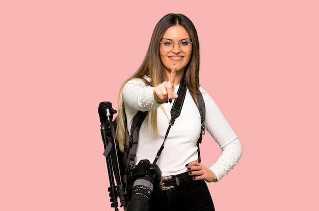 Mulher jovem fotógrafo mostrando e levantando um dedo na parede rosa isolada