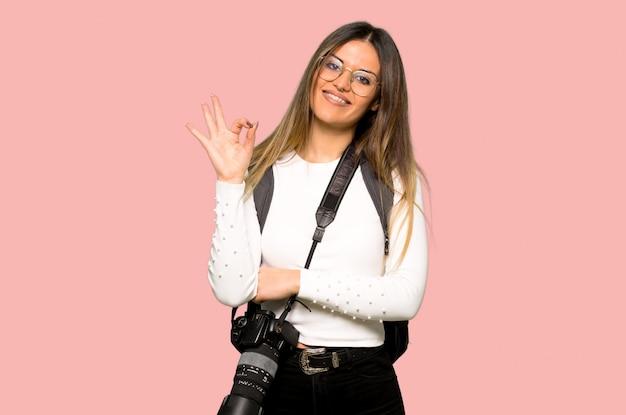 Mulher jovem fotógrafo mostrando um sinal de ok com os dedos na parede rosa isolada