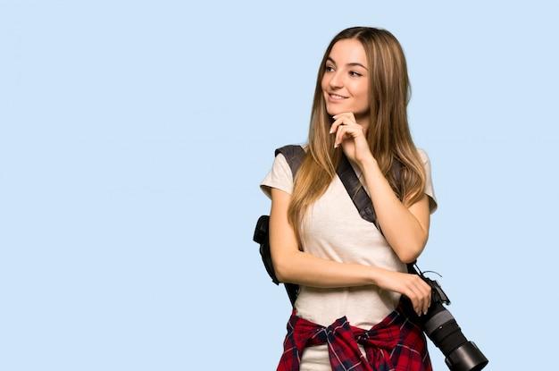 Mulher jovem fotógrafo olhando para o lado com a mão no queixo na parede azul isolada