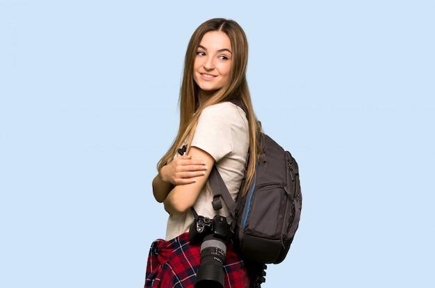 Mulher jovem fotógrafo olhando por cima do ombro com um sorriso no fundo azul isolado