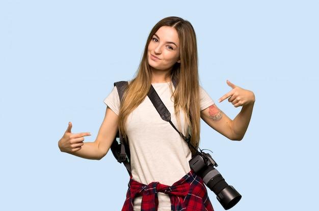 Mulher jovem fotógrafo orgulhoso e satisfeito em se amar conceito na parede azul isolada