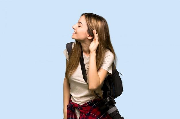 Mulher jovem fotógrafo ouvindo algo, colocando a mão na orelha na parede azul
