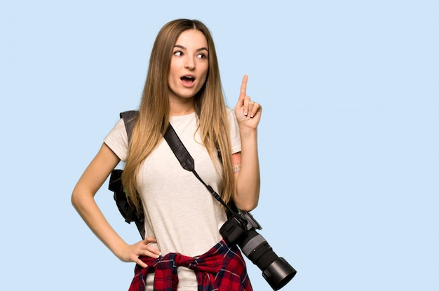 Mulher jovem fotógrafo pensando uma idéia apontando o dedo na parede azul isolada