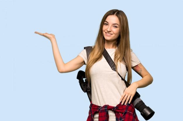 Mulher jovem fotógrafo segurando copyspace imaginário na palma da mão para inserir um anúncio no fundo azul isolado