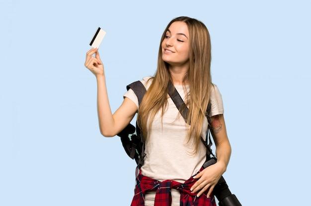 Mulher jovem fotógrafo segurando um cartão de crédito e pensando no fundo azul isolado