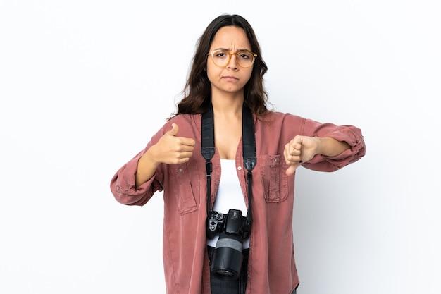 Mulher jovem fotógrafo sobre fundo branco isolado, fazendo sinais de bom-ruim. indeciso entre sim ou não