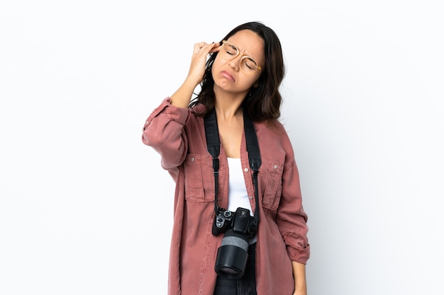 Mulher jovem fotógrafo sobre parede branca com dor de cabeça