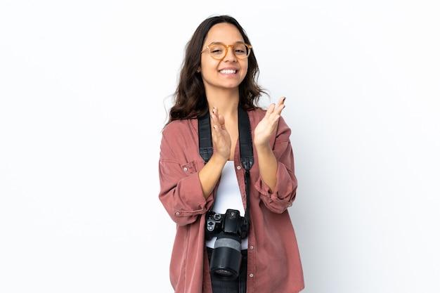 Mulher jovem fotógrafo sobre parede branca isolada aplaudindo após apresentação em uma conferência