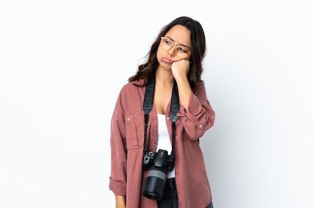 Mulher jovem fotógrafo sobre parede branca isolada com expressão cansada e entediada