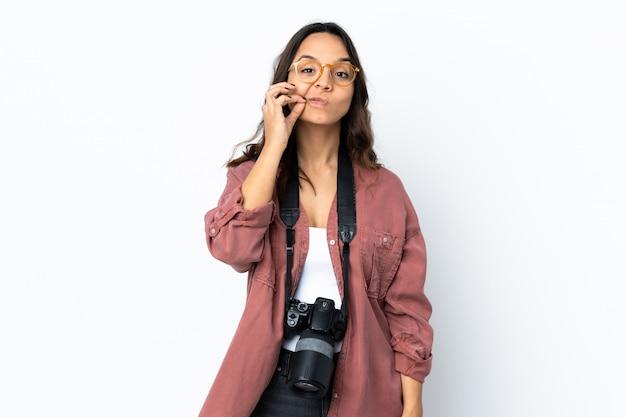 Mulher jovem fotógrafo sobre parede branca isolada, mostrando um sinal de gesto de silêncio