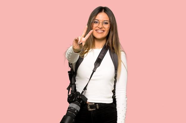 Mulher jovem fotógrafo sorrindo e mostrando sinal de vitória na parede rosa isolada