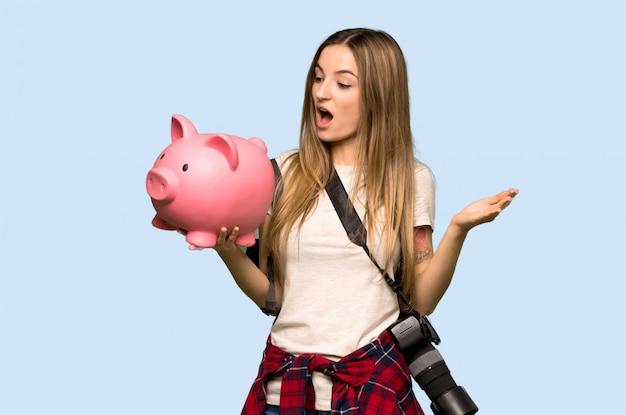 Mulher jovem fotógrafo surpreendida enquanto segura um piggybank na parede azul isolada