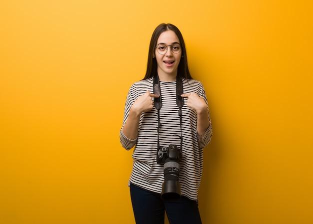Mulher jovem fotógrafo surpreendido, sente-se bem sucedido e próspero