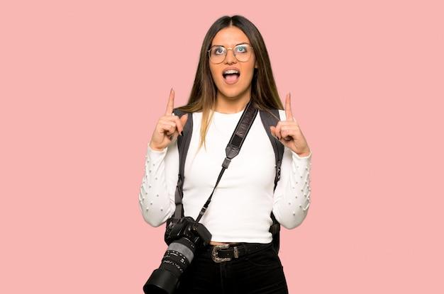 Mulher jovem fotógrafo surpreso e apontando para cima no fundo rosa isolado