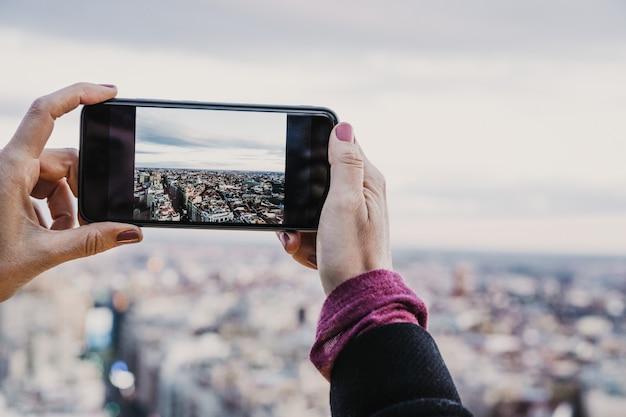 Mulher jovem fotógrafo tirando uma foto da cidade de madrid, de um telhado alto. viagem, tecnologia