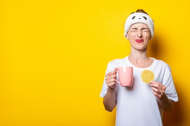 Mulher jovem franziu os olhos com uma xícara de café e um waffle belga em um fundo amarelo