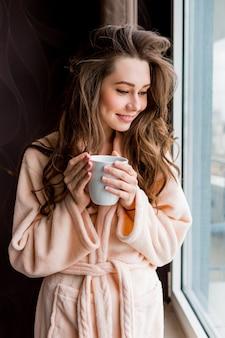 Mulher jovem fresca em um roupão rosa beber chá, olhando pela janela.