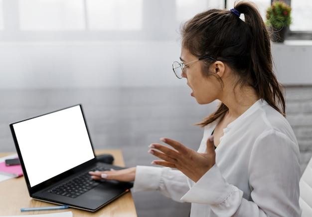 Mulher jovem frustrada trabalhando em casa Foto gratuita