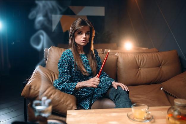 Mulher jovem fumando narguilé no restaurante, fumaça de tabaco na boate