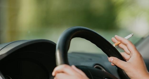 Mulher jovem fumando um cigarro enquanto dirige um carro, conceito de transporte