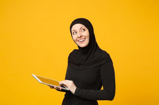 Mulher jovem funcionário árabe muçulmano em roupas pretas de hijab segurar e trabalhar computador tablet pc isolado no retrato de parede amarela. conceito de estilo de vida religioso de pessoas. .