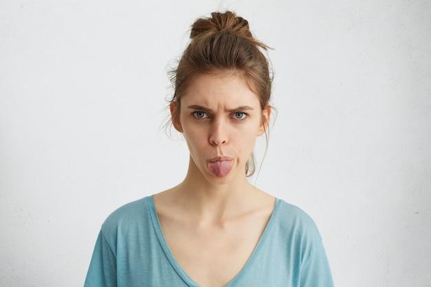 Mulher jovem furiosa mostrando seu nojo e desgosto com expressão sombria, língua de fora se recusando a fazer algo