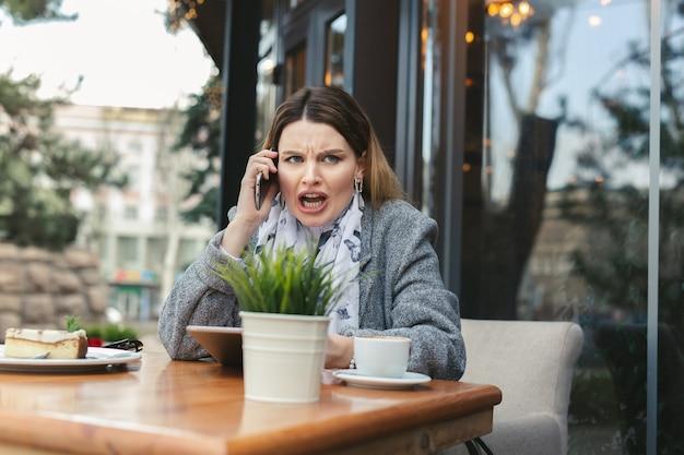 Mulher jovem furiosa resolvendo problemas de negócios, gritando durante uma conversa por telefone
