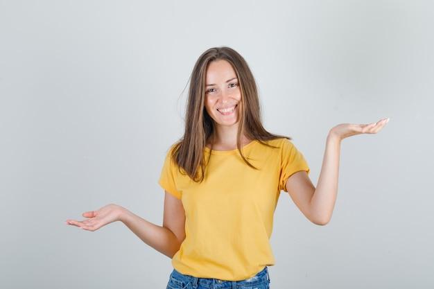 Mulher jovem gesticulando com as palmas das mãos, tentando decidir na camiseta