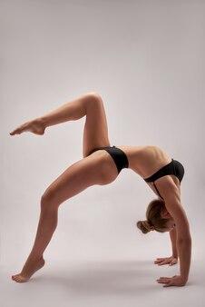 Mulher jovem ginasta magro em roupas esportivas em pé de cabeça para baixo na parede branca.