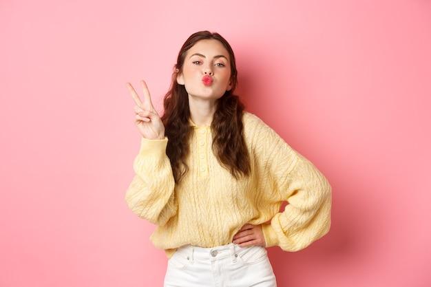 Mulher jovem glamour franzir os lábios, beijando o rosto e fazendo o sinal v, mostrar um gesto de paz, em pé contra a parede rosa.