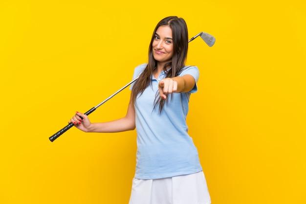 Mulher jovem golfista aponta o dedo para você com uma expressão confiante