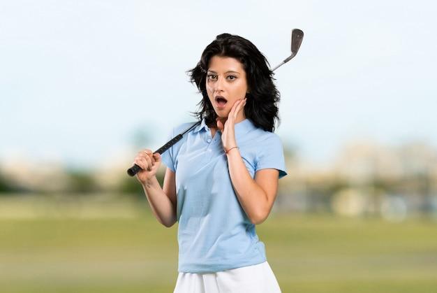 Mulher jovem golfista com surpresa e expressão facial chocada ao ar livre