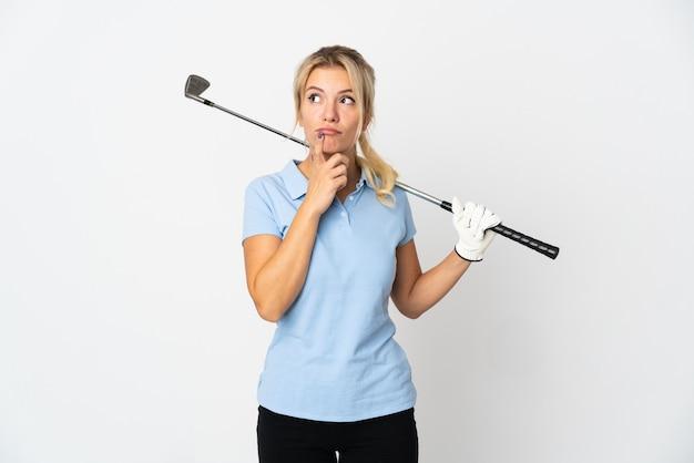 Mulher jovem golfista russa isolada no fundo branco com dúvidas enquanto olha para cima