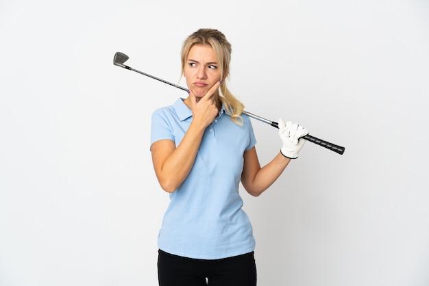 Mulher jovem golfista russa isolada no fundo branco com dúvidas