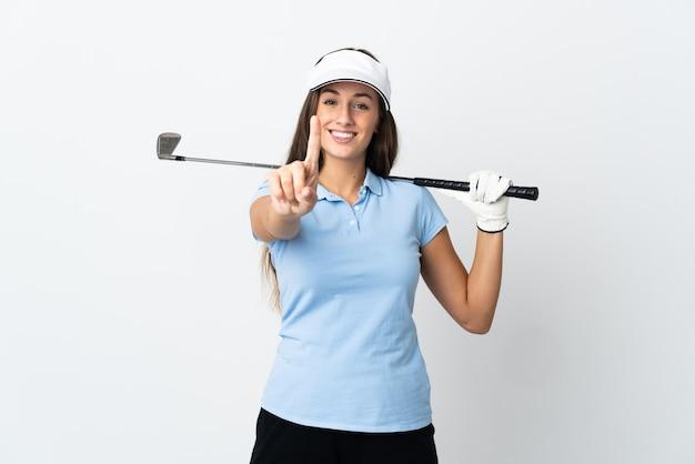Mulher jovem golfista sobre fundo branco isolado, mostrando e levantando um dedo