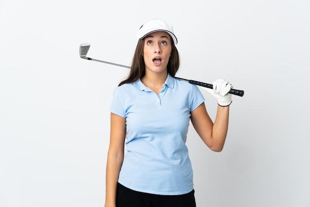 Mulher jovem golfista sobre fundo branco isolado, olhando para cima e com expressão de surpresa