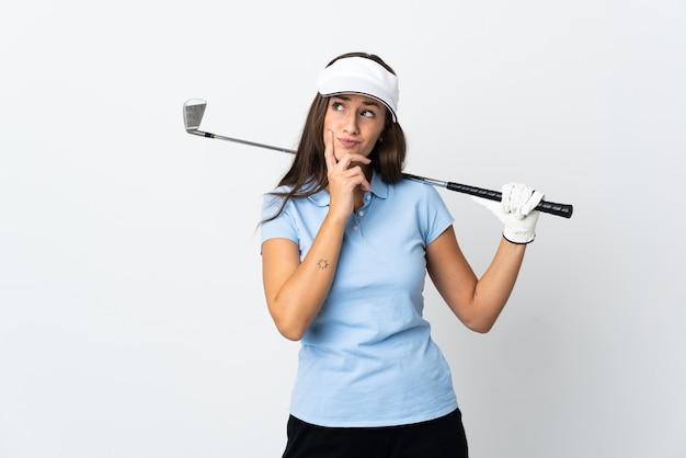Mulher jovem golfista sobre fundo branco isolado tendo dúvidas enquanto olha para cima